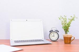 Laptop, Tasse und Blume auf dem Schreibtisch