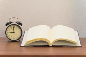 Buch und Wecker den Schreibtisch