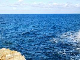 blaue Wellen in der Nähe einer Klippe foto