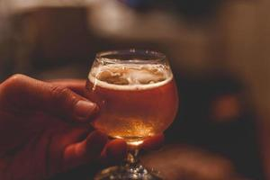 Person, die ein Glas Bier hält foto