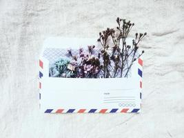ein Vintage Umschlag mit kleinen süßen Blumen. Geschenkbox-Grußkarte für Valentinsgrüße auf weißem Leinenhintergrund