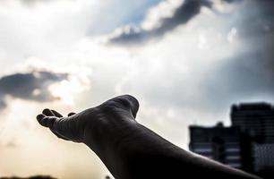 Hand greift in den Himmel. Hand erreicht den Himmel, Verbindung, Erde, weit weg, Hände. Hand greift in der Dämmerung nach dem Himmel foto