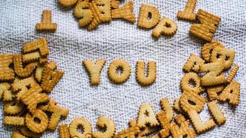 Finden Sie Konzept Cookies in Form der Alphabet-Perspektive. Glücklich von hausgemachten Cookies auf dunkelweißem Hintergrund. Happy Cookies-Konzept.