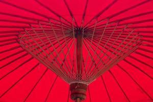 unter rotem Regenschirm. asiatische Hintergrundidee der Bambusstruktur