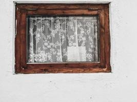 rustikales Fenster mit weißen Spitzenvorhängen. alte Vintage Fenster Grunge Zementwand foto