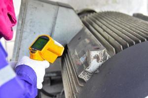 Arbeiter messen die Temperatur des Motors foto