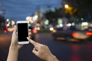 Hand, die Smartphone auf unscharfem Hintergrundtransport hält.