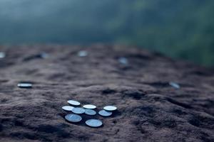 Geldmünze auf den Stein gelegt. wirtschaftliches Konzept ausdrücken foto