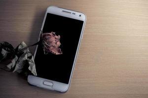trockene Rosen auf dem Tisch mit einem Handy