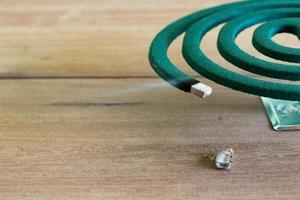 grünes Mückenschutzbrennen und weißer Rauch auf Holztisch mit grünem Unschärfelicht.