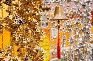 kleine goldene Glocken hängen im thailändischen Tempel foto