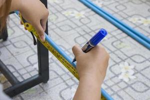 Arbeiter verwenden ein Maßband, um die Länge des PVC-Rohrs zu messen