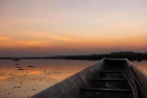 Holzboot am Fluss mit dem Sonnenuntergang festgemacht.