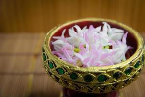 bunte Kunstblumen in einem luxuriösen goldenen Tablett platziert foto