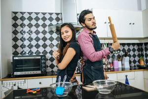 attraktives Paar, das in ihrer Küche zu Hause kocht foto