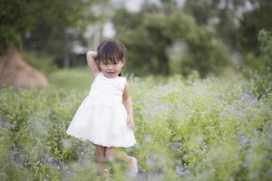 glückliches kleines Mädchen, das in der Wiese in einem weißen Kleid steht