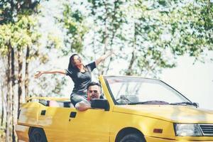 glückliches Paar, das das Verdeck unten im Cabrio genießt foto