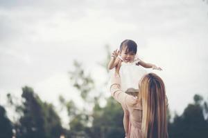 Mutter und kleine Tochter spielen zusammen auf einer Wiese foto
