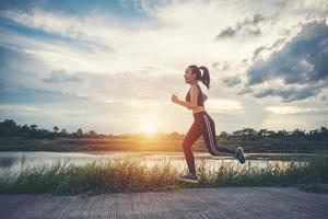 eine junge glückliche Läuferin, die draußen joggt