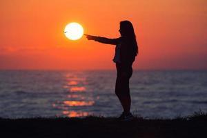 Mädchen, das die Sonne berührt foto