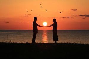 Silhouette eines Paares bei Sonnenuntergang foto