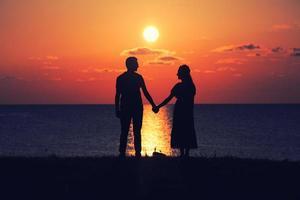 zwei Leute, die Hände bei Sonnenuntergang halten foto