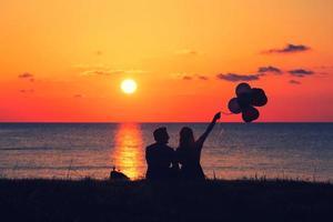 zwei Leute, die Luftballons auf dem Sonnenuntergang halten foto