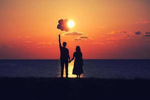 die Liebenden, die den Sonnenuntergang mit Luftballons betrachten foto