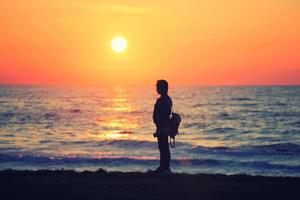 ein Mädchen beobachtet den Sonnenuntergang foto