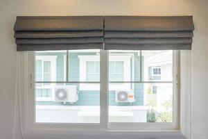 Innendekoration des grauen Vorhangs im Wohnzimmer mit Sonnenlicht