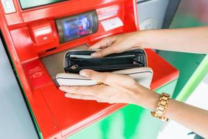 Nahaufnahme der Hand mit Brieftasche, die Bargeld am Geldautomaten-, Finanz-, Geld-, Bank- und Personenkonzept abhebt