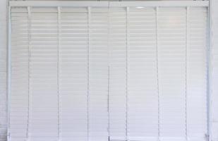 Sonnenschutz Jalousie der weißen Farbe am Fenster an einem hellen sonnigen Tag