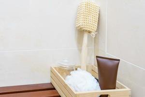 Set Badzubehör auf Holzkorb. Badepuff, Luffa Spa Kit, Duschgel, Lotion