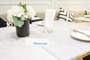reservierter Teller auf einem Esstisch in einem Restaurant mit eleganter Tischdekoration