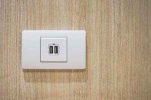 USB-Buchsenanschluss mit USB-Beschilderungssymbol auf Holzwandhintergrund, zur Verwendung vorbereitet.