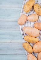 Draufsicht von weißen gelben und rostroten Kartoffeln auf der rechten Seite und hölzernem Hintergrund mit Kopienraum