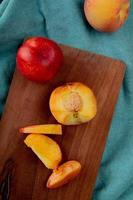 Draufsicht des ganzen geschnittenen geschnittenen Pfirsichs mit Messer auf Schneidebrett und ganzen Pfirsich auf blauem Stoffhintergrund