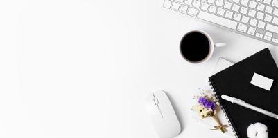 Minimaler Bürotisch mit Tastaturcomputer, Kaffeetasse, Maus, weißem Stift, Baumwollblumen, Radiergummi, weißem Stoff auf einem weißen Tisch mit Kopierraum für die Eingabe Ihres Textes, weiße Arbeitsplatzzusammensetzung, flache Lage, Draufsicht foto