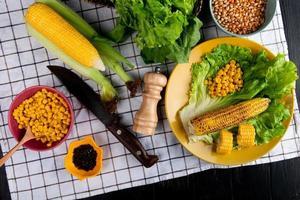 Draufsicht auf ganze und geschnittene Körner und Maissamen mit Salat in Platte und Spinatmesser schwarzer Pfeffer auf kariertem Stoff und schwarzem Hintergrund
