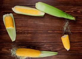 Mais auf hölzernem Hintergrund mit Kopienraum foto