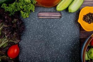 Draufsicht auf geschnittenes und ganzes Gemüse als Tomaten-Basilikum-Minze-Gurken-Koriander mit schwarzem Pfeffer und Schneidebrett auf Holzhintergrund foto