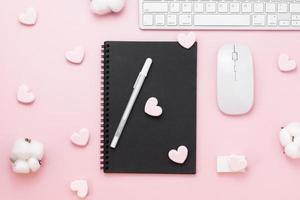 Minimaler Bürotisch mit Herz-Büroklammer, Tastaturcomputer, Maus, weißem Stift, Baumwollblumen, Radiergummi auf einem rosa Pastelltisch mit Kopierraum für die Eingabe Ihres Textes, Valentinstagskonzept, flache Lage, Draufsicht