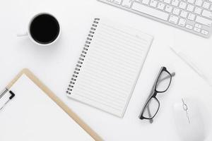 Minimale Büro-Tisch-Draufsicht mit Büromaterial und Kaffeetasse auf einem weißen Tisch mit Kopierraum, weißer Arbeitsplatzzusammensetzung, flache Lage