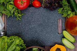 Draufsicht auf geschnittenes und ganzes Gemüse als Tomaten-Basilikum-Minze-Gurken-Salat-Koriander mit schwarzem Salzpfeffer und Schneidebrett auf hölzernem Hintergrund foto