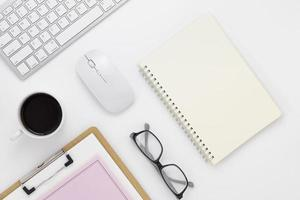 Minimale Büro-Tisch-Draufsicht mit Büromaterial und Kaffeetasse auf einem weißen Tisch mit Kopierraum, weißer Arbeitsplatzzusammensetzung, flache Lage foto