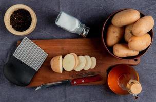 Draufsicht auf geschnittene Kartoffel und Messer mit Kartoffelchipschneider auf Schneidebrett mit anderen in Schüssel Salz schwarzer Pfefferbutter auf grauem Stoffhintergrund