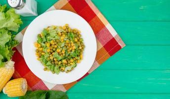 Draufsicht der Platte der gelben Erbse und des geschnittenen Salats mit Maisspinat-Salatsalz auf Stoff und grünem Hintergrund mit Kopienraum foto