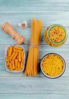 Draufsicht auf verschiedene Arten von Makkaroni als Tagliatelle Spaghetti Fadennudeln Ziti und andere mit Knoblauchsalz auf Holzhintergrund foto
