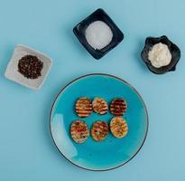 Draufsicht von gebratenen Kartoffelscheiben in Platte mit schwarzem Pfeffersalz und Mayonnaise auf blauem Hintergrund