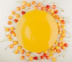 Draufsicht von roten und gelben Kirschen mit leerer gelber Platte in der Mitte auf weißem Hintergrund foto
